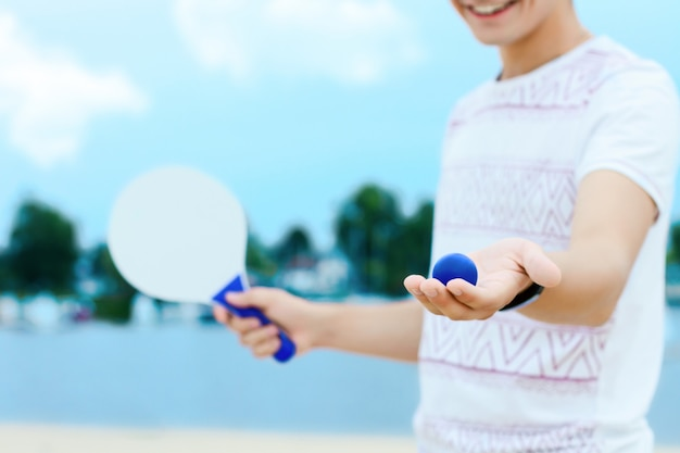 軽い服を着た若い笑みを浮かべて男は彼の手に白いラケットとボールを保持しています。