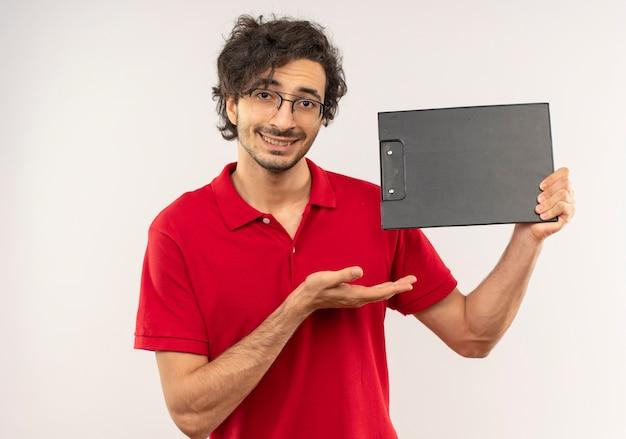 光学メガネと赤いシャツを着た若い笑顔の男は、白い壁に分離されたクリップボードを保持し、ポイントします。