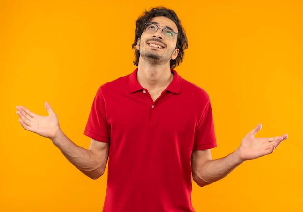 Молодой улыбающийся человек в красной рубашке с оптическими очками держит руки открытыми и смотрит вверх изолированно на оранжевой стене