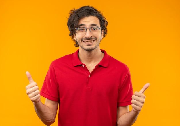 オレンジ色の壁に分離された光学メガネの親指を立てて赤いシャツを着た若い笑顔の男