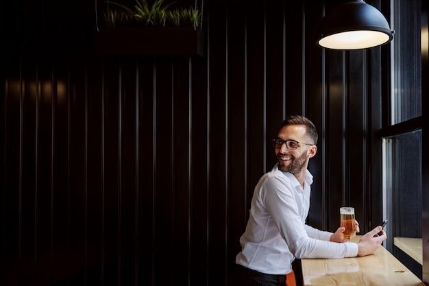 ウィンドウの横のパブに座って、ビールのグラスを持って、肩越しに見ているシャツを着た若い笑みを浮かべて男。彼は友達に会った。