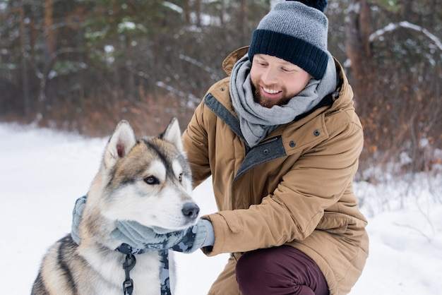 雪に覆われた公園や森の寒さの中で純血種のシベリアンハスキー犬を抱きしめるウィンターウェアの若い笑顔の男