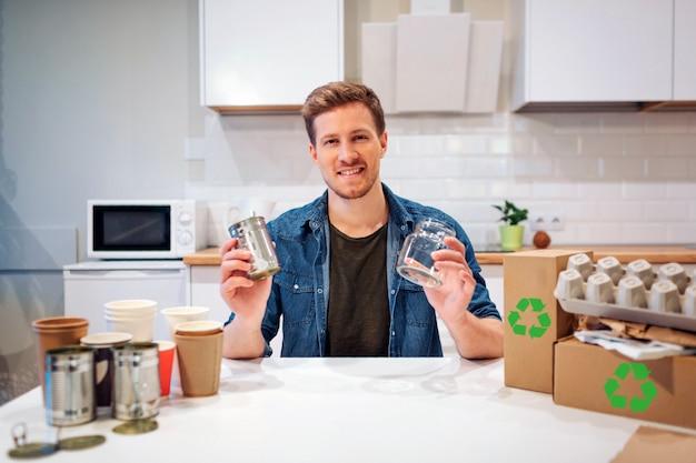 若い笑みを浮かべて男は空のガラス瓶や金属缶を並べ替えます