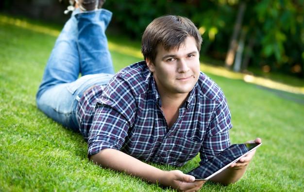 公園の芝生の上に横たわると、デジタル タブレットを使用して若い笑顔の男