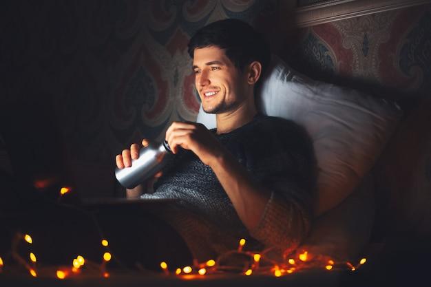 Молодой улыбающийся человек, лежащий на подушке на кровати в темной комнате дома, держа в руках многоразовую алюминиевую термо-бутылку с водой