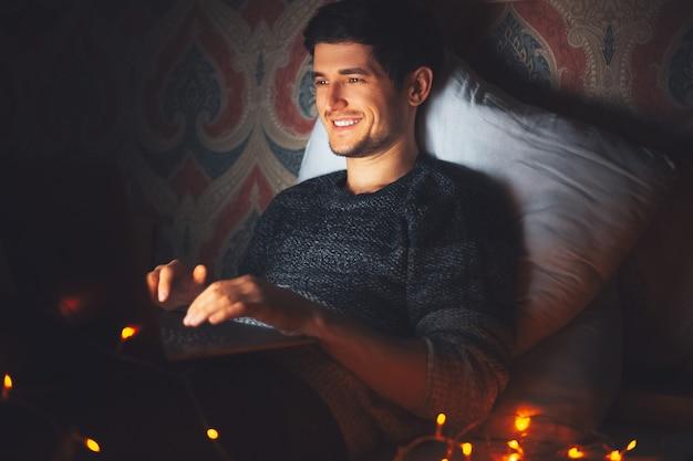 Молодой улыбающийся человек, лежа на подушке на кровати с ноутбуком в темной комнате дома с гирляндами.