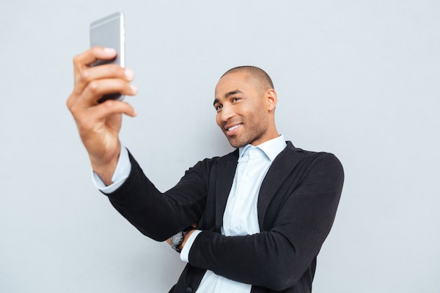 Young smiling man making selfie photo on smartphone isolated