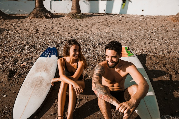 Young smiling man near cheerful woman and surf boards on shore