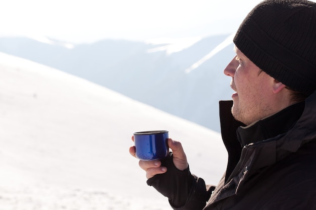 Young smiling man photographer in winter clothing drinking tea from thermos and smiling in sunlight with white snow background