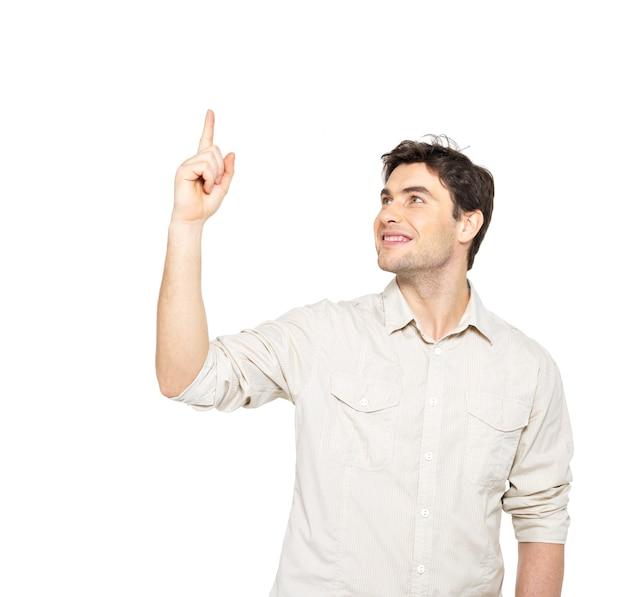 Il giovane uomo sorridente indica con il dito su qualcosa in casuals isolato su priorità bassa bianca.
