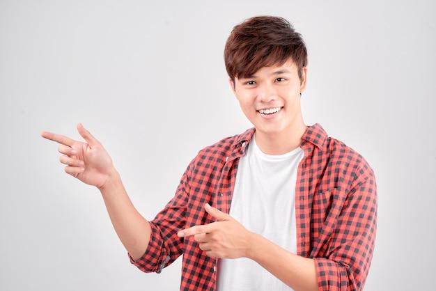 若い笑顔の男は、白い背景で隔離の右側に指で指しています。