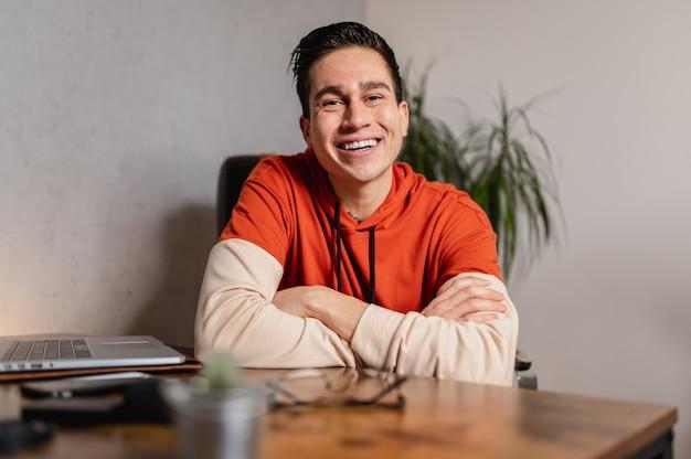 Портрет молодой улыбающийся человек, глядя в камеру с уверенным лицом, сидя на стуле в офисной комнате с повседневной одеждой.