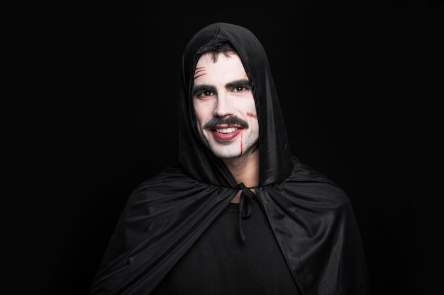 Young smiling man posing in black halloween costume