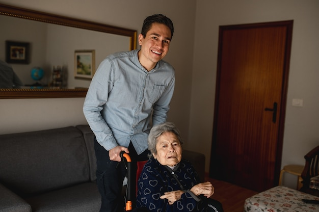 Young smiling man pushing wheelchair with old sick aged woman. family, home care concept.
