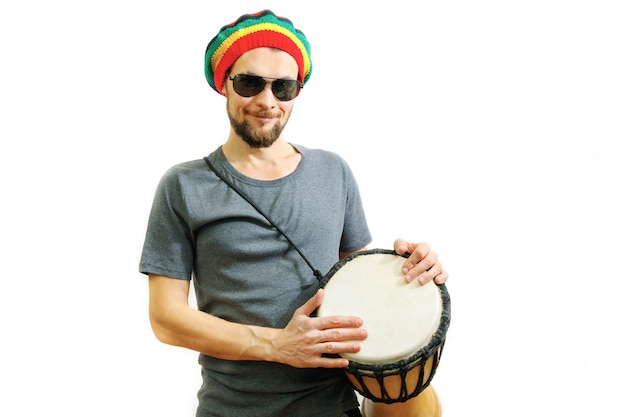 Young smiling man in rasta hat and grey tshirt on white background with djembe african drum