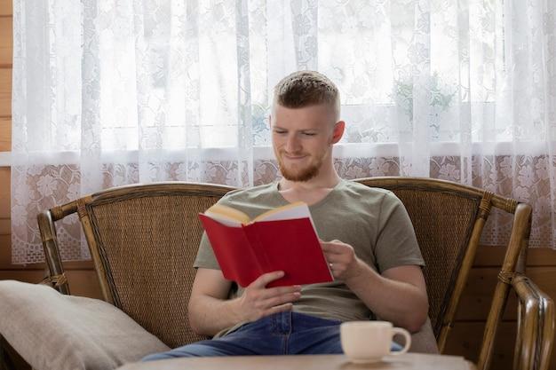 Молодой улыбающийся человек читает книгу с красной крышкой на плетеной скамейке в деревянном доме сельской местности