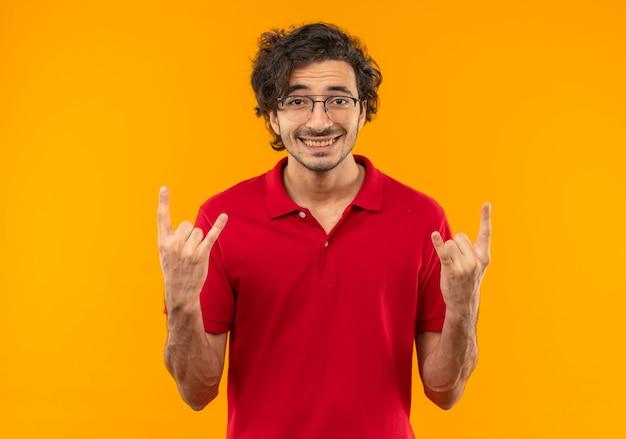 Giovane uomo sorridente in camicia rossa con occhiali ottici gesti le corna con le mani isolate sulla parete arancione