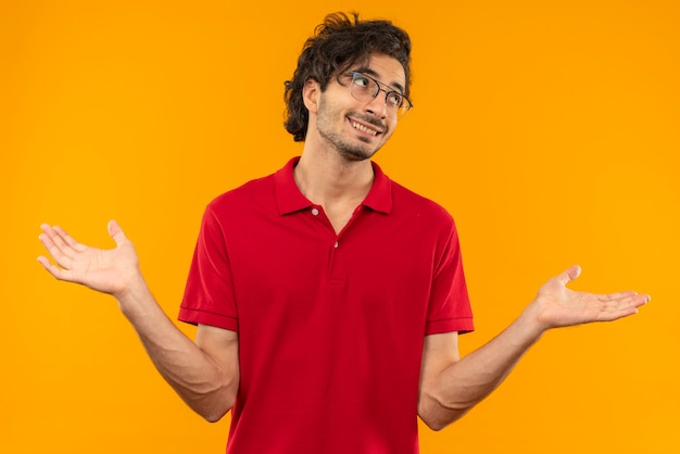 Young smiling man in red shirt with optical glasses holds hands open isolated on orange wall