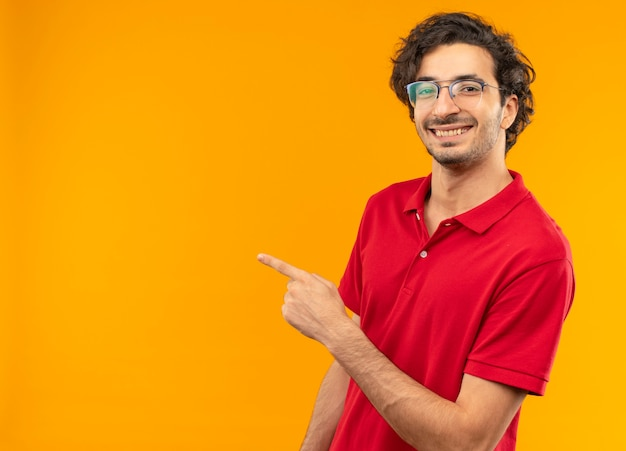 Young smiling man in red shirt with optical glasses points at side and looks isolated on orange wall