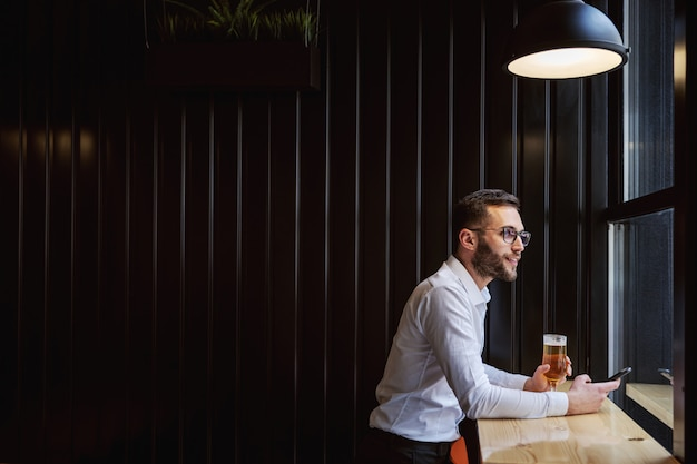 Young smiling man in shirt sitting next to window in pub, holding beer and phone and enjoying free time after work.