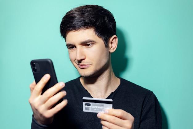 アクアメンテカラーの壁にスマートフォンとクレジットカードでオンラインショッピングの若い笑顔の男。