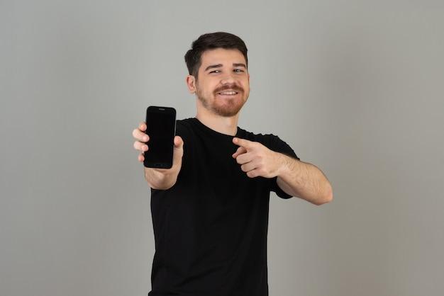 Молодой улыбающийся человек показывает свой телефон камере на сером.