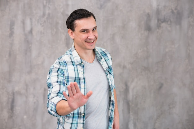 Young smiling man showing stop gesture