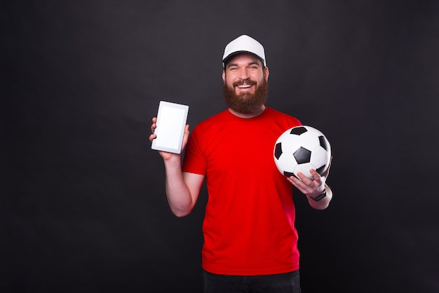 Young smiling man showing tablet and holding soccer ball over black