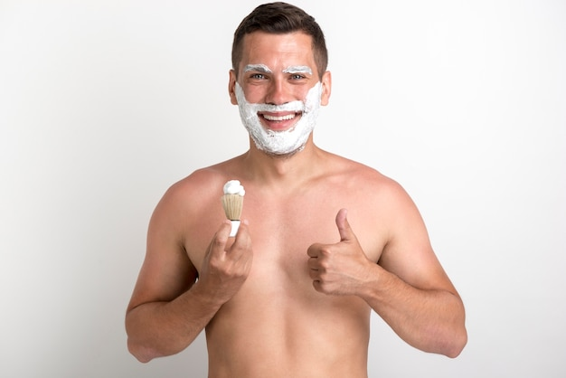 Young smiling man showing thumb up gesture while shaving