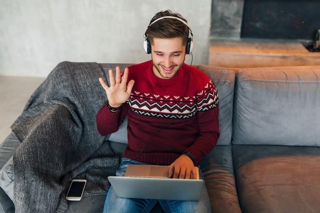 Молодой улыбающийся человек сидит дома зимой, разговаривает в интернете, машет рукой, здоровается, одет в красный свитер, работает на ноутбуке, фрилансер, слушает наушники, учится онлайн