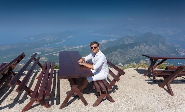 Молодой улыбающийся человек, сидящий на скамейке на вершине высокой горы в солнечный день