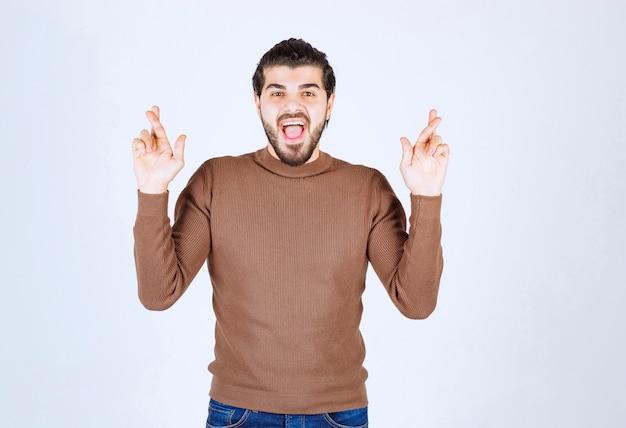 Giovane uomo sorridente in piedi con le dita incrociate sul muro bianco.