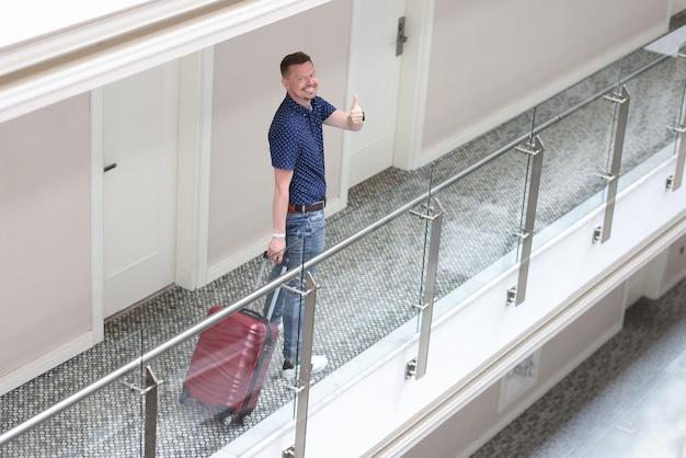 웃는 젊은이 호텔 복도에 서서 엄지 손가락 제스처를 보여줍니다