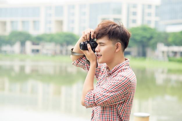 Молодой улыбающийся человек фотографирует во время прогулки по городу.