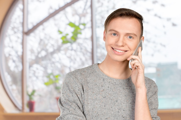 Молодой улыбающийся человек разговаривает по мобильному телефону
