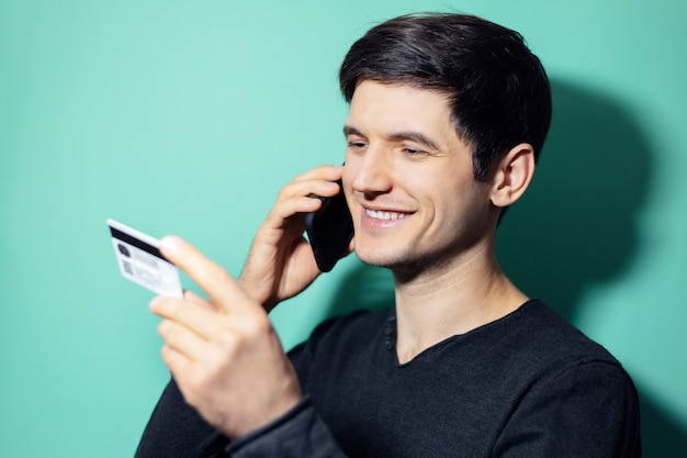 Young smiling man talking on smartphone and looking at his credit card in hand on wall of aqua menthe color.