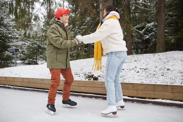 屋外のスケートリンクでスケートをするように女性に教える若い笑顔の男