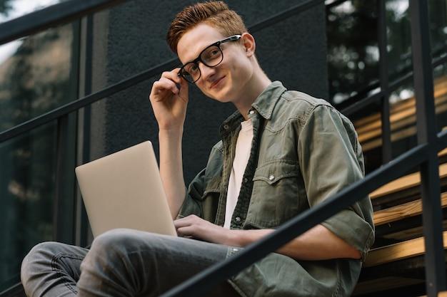Молодой улыбающийся человек с помощью портативного компьютера на лестнице на улице