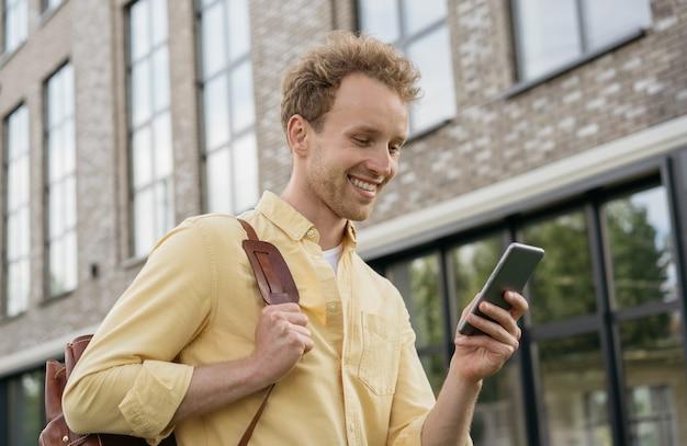 야외에서 온라인 쇼핑을 하는 휴대전화를 사용하여 웃고 있는 젊은 남자