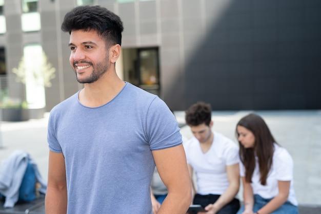 人々のグループの前を歩いている若い笑顔の男