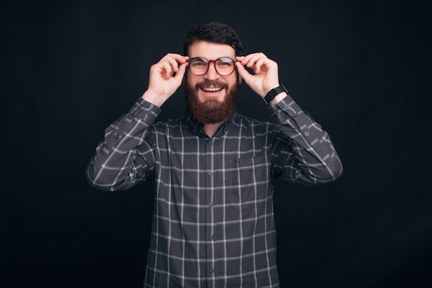 Young smiling man wearing beard is putting on his eyeglasses.