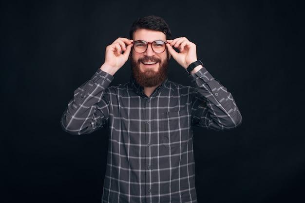 Молодой улыбающийся человек носить бороду надевает очки.