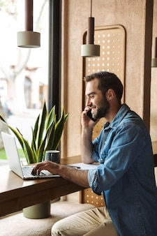 Young smiling man wearing denim shirt talking on cellphone with laptop and clipboard while working in cafe indoors