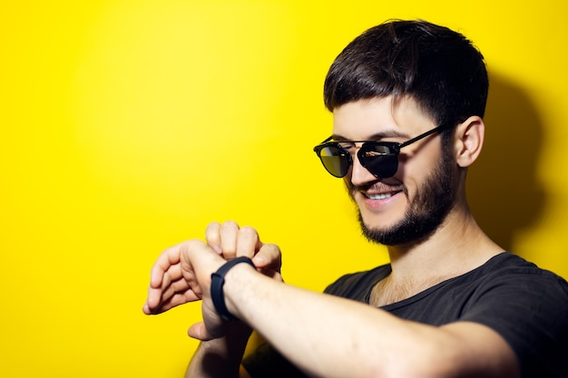 Young smiling man wearing sunglasses, setting smartwatch on yellow wall.