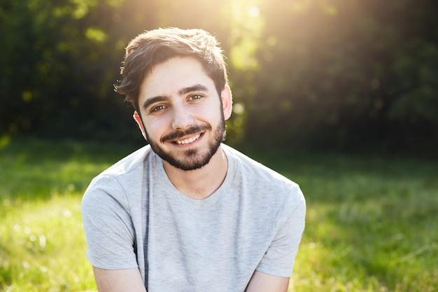 グリーンランドに座っているカジュアルなtシャツを着ている黒い髪、濃い眉毛、魅力的な目とひげを持つ若い笑顔の男