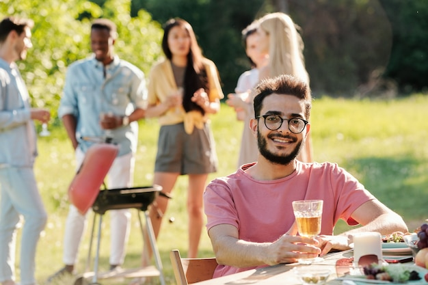 Young smiling man with glass of wine looking at you while sitting by served table on of friends talking and making barbecue