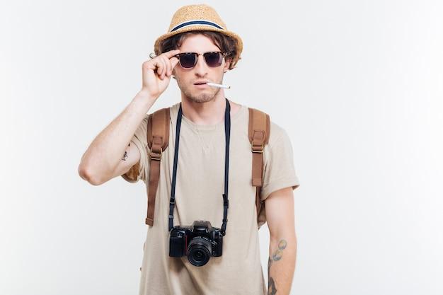 Молодой улыбающийся человек с ретро камерой для некурящих сигарет, изолированные на белом фоне