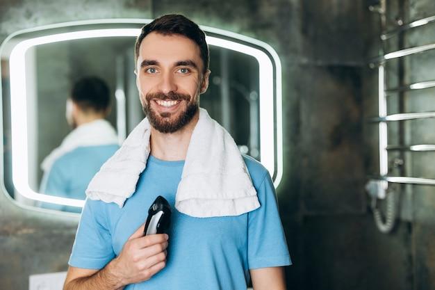 Молодой улыбающийся человек с полотенцем, держащий новую бритву рано утром в ванной