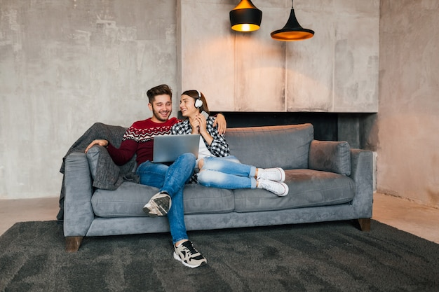 Young smiling man and woman sitting at home in winter looking in laptop with happy face expression, using internet, couple on leisure time together, positive emotion, dating