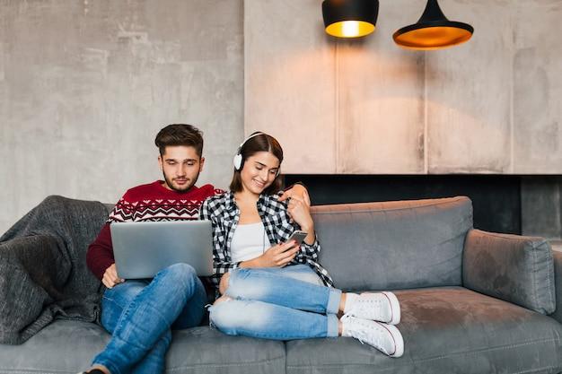 Giovane uomo sorridente e donna seduta a casa in inverno, lavorando al laptop, tenendo lo smartphone, ascoltando le cuffie, coppia nel tempo libero che trascorre del tempo online, libero professionista, incontri